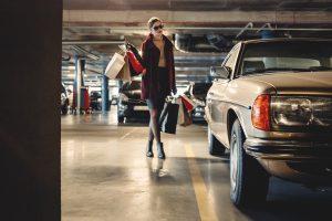 Mujer cargada con bolsas de la compra llegando a un coche