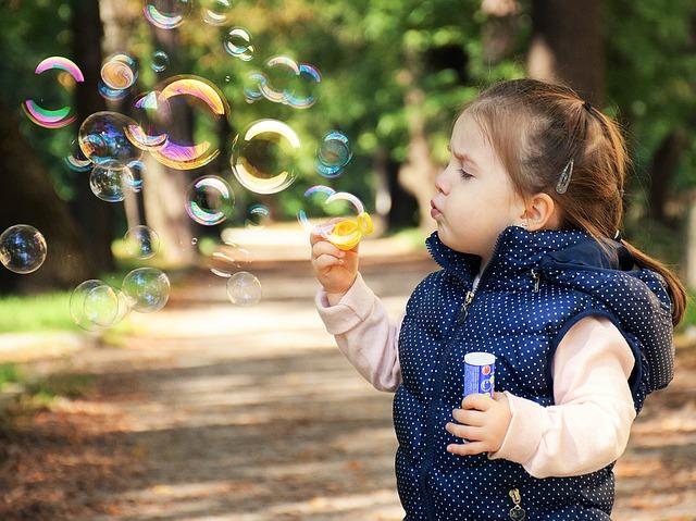 Imagen de una niña haciendo pompas de jabón