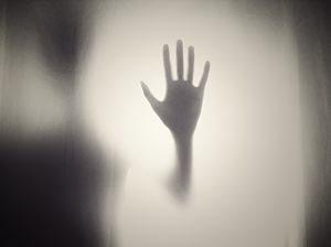 Imagen de una mano frente a un cristal
