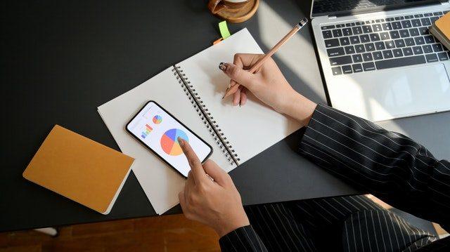persona escribiendo y tocando la pantalla del movil junto a un ordenador