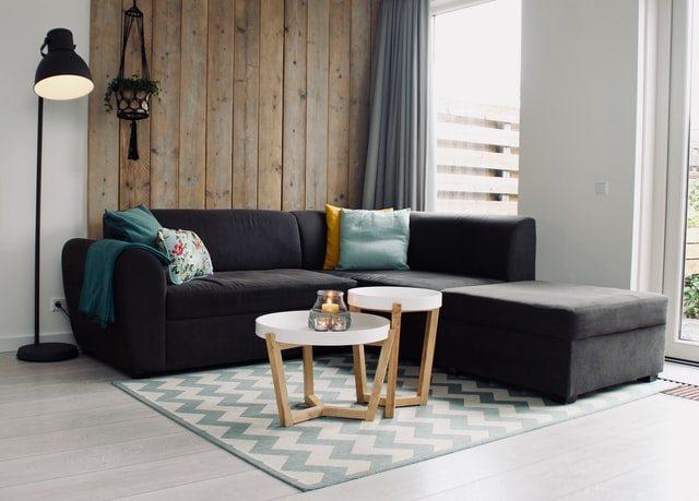 Sofá esquinero junto con mesa y lampara de pie en un salón moderno