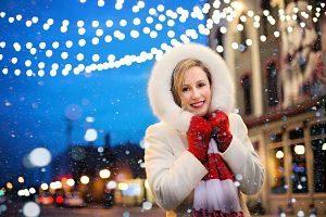 Imagen de una mujer bajo las luces de Navidad