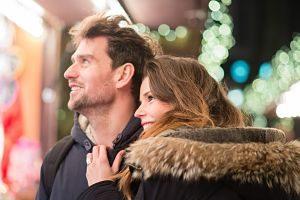 Imagen de una pareja mirando un stand de un mercado de navidad