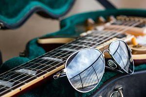 Imagen de una guitarra eléctrica y unas gafas de sol