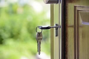 Imagen de una puerta de una casa con una llaves en la cerradura