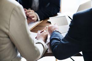 Imagen de unas personas firmando un documento