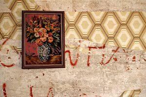 Imagen de una pared con un cuadro y una pintada