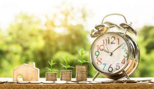 Imagen de dinero, una casita de madera de juguete y un reloj