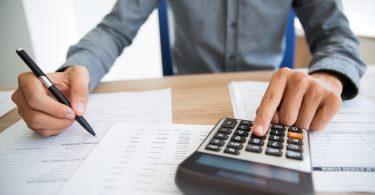 Primer plano de las manos masculinas usando la calculadora para examinar el informe. Contador irreconocible contando las ganancias. Empresario analizando documentos. Concepto de papeleo