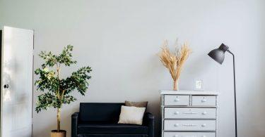 Habitación con sofá, cómoda, lámpara y armario