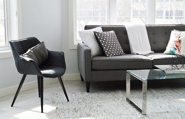 rincón de un salón con una butaca negra, un sofá gris y una mesita de cristal
