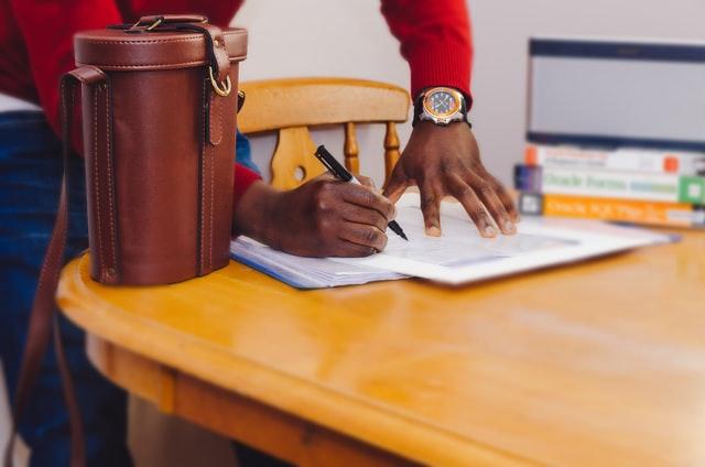 Mano de persona firmando unos papeles con un bolso al lado