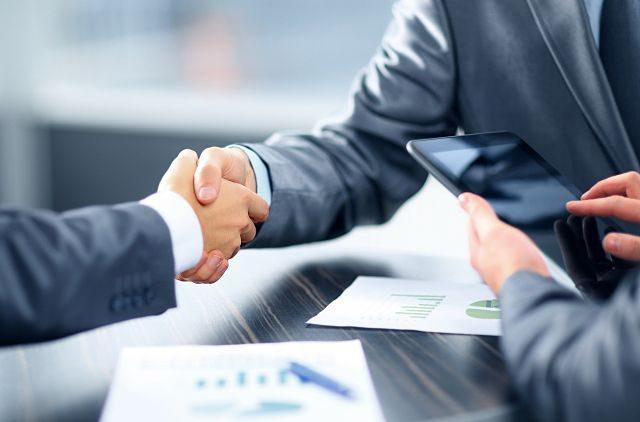 Imagen de dos hombres dándose la mano en un banco