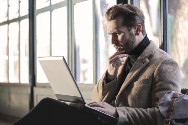 Hombre con barba con gesto de pregunta frente a un ordenador portátil