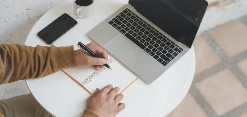 mano de persona escribiendo en una libreta al lado de un ordenador y un teléfono móvil y un café