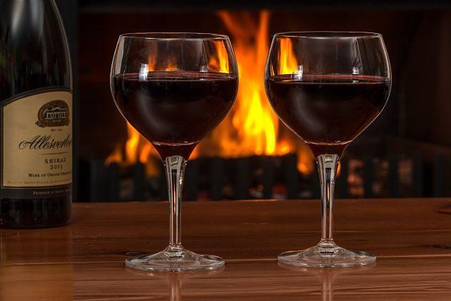 Imagen de dos copas de vino junto a una chimenea
