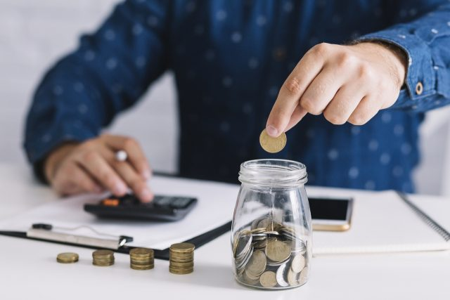 Chico con camisa azul poniendo monedas en un bote de cristal mientras hace cuentas en una calculadora