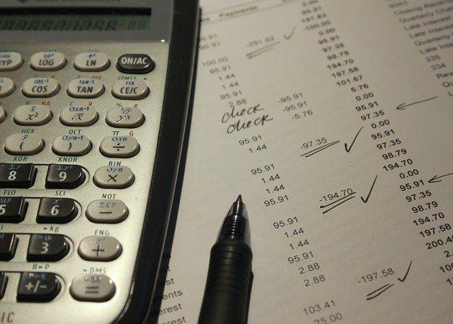 calculadora sobre hoja con cálculos y un bolígrafo