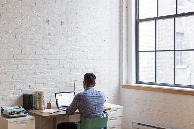 chico de espaldas sentado frente a un ordenador