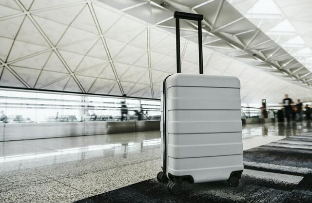 maleta de ruedas blanca en una estación