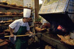 Cocinero asando al horno un cochinillo en la cocina de Casa Botín